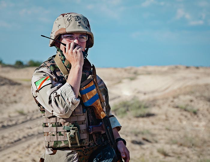 soldier in field talking on a radio