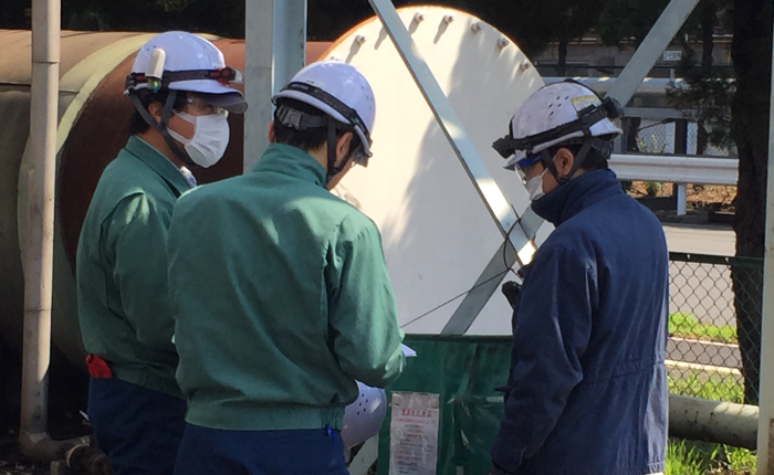 three workers in hardhats standing in a circle