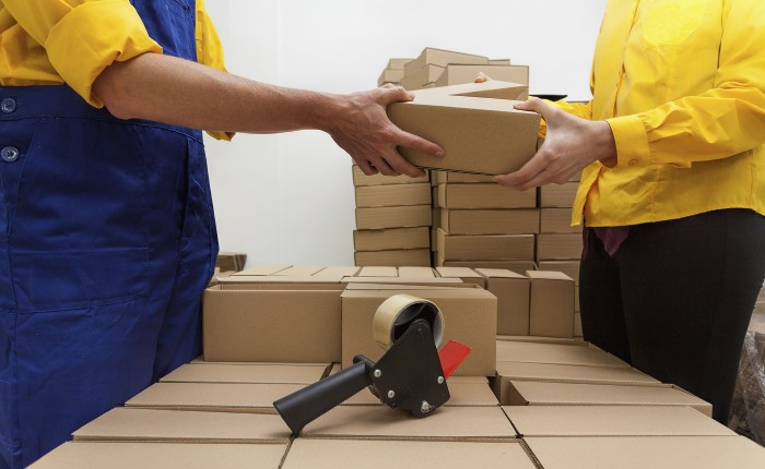 A pile of brown cardboard boxes; a hand-held tape dispenser; one person in yellow handing a box to another person in yellow.